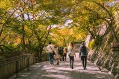 People waking through Kiyomizu Garden with back lit trees close to sunset. Kyoto, Japan - November 2, 2018: People walking through Kiyomizu Garden with back lit royalty free stock images