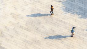 people walk on across the pedestrian concrete landscape with black silhouette shadow on ground (top aerial view) stock image