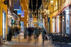 Free People Walk Along A Street Illuminated By Christmas Lights. Royalty Free Stock Images - 164060329