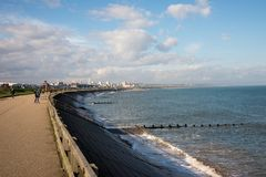 People walk along Aberdeen coast and a view ofa city in a distance Stock Images