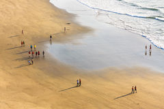 People walk along the beach in the summer day Stock Photos