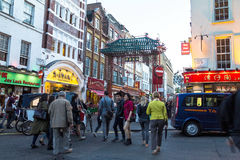 People walk along a busy shopping street in London Chinatown. Royalty Free Stock Photography