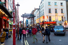 People walk along a busy shopping street in London Chinatown. Royalty Free Stock Images