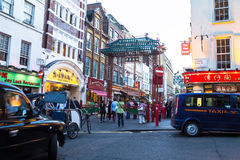 People walk along a busy shopping street in London Chinatown. Stock Images