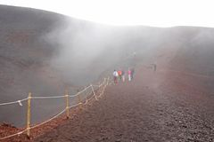 People Walk along the crater of Mount Etna. Black Volcanic Earth and Thick Fog on Mount Etna. Place for Text. The island of Sicily. Italy stock photos