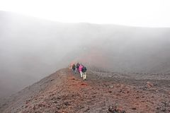 People Walk along the crater of Mount Etna. Black Volcanic Earth and Thick Fog on Mount Etna. Place for Text. The island of Sicily. Italy royalty free stock images