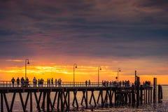 People walk along Glenelg jetty at sunset Royalty Free Stock Image