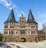 People walk along Holstentor gate Stock Image
