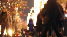 People walk along a lit street. Crowd. Girl`s Photoshoot. People walk along a lit street. Christmas garlands. Crowd. Girl. Photoshoot stock footage