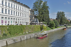 People walk along Ljubljanica river in Ljubljana, Slovenia Stock Image