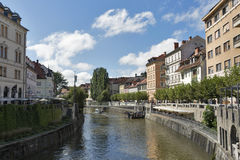 People walk along Ljubljanica river in Ljubljana, Slovenia Royalty Free Stock Photo