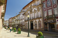 People walk along the one of most known street in Guimaraes, Portugal Stock Photos