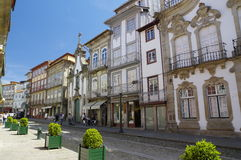 People walk along the one of most known street in Guimaraes, Portugal. GUIMARAES, PORTUGAL - APRIL 23 2015: People walk along the one of most known street on Royalty Free Stock Photos