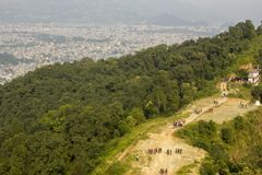 A people walk along the path to the top of the mountain with a green forest on the background of the city in the valley below the stock photos