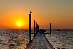 People walk along the pier to the beach at sunrise. Workers sailed on boats stock photo