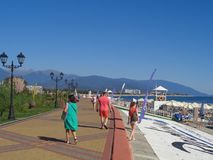 People walk along promenade, seaside Sochi, Russia. Sunny day, people walk along waterfront and rest on the beach Stock Image