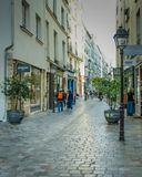 People walk along Rue des Rosiers in the Marais neighborhood in Paris stock photo