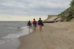 People walk along the seashore Royalty Free Stock Photo