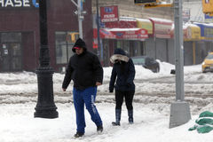 People walk along street during snow storm Royalty Free Stock Photo