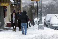 People walk along street during snow storm Royalty Free Stock Images