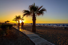 People walk along the sunset beach Stock Images