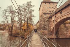 People walk along a wooden suspension bridge across the river in the historic city of Nuremberg with historical walls. Royalty Free Stock Photo