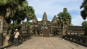 Angkor ancient temple in Cambodia. People walk by ancient temple in Angkor stock video footage