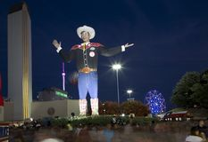 People walk around Big Tex at Fair Park night. People walk around Big Tex on Fair Park night, State Fair of Texas city Dallas USA Royalty Free Stock Photo
