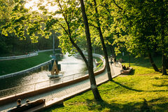 People walk around the city park during sunset in Royalty Free Stock Images