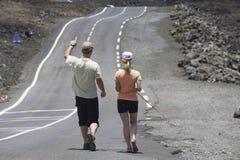 People walk by the asphalt road over volcanic lava in Sainte-Rose De La Reunion, France. Stock Photos
