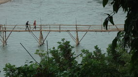 People walk bamboo bridge over river in Luang Prabang stock video