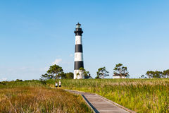 People Walk on Boardwalk Through Marshland at Bodie Island Lighthouse stock images