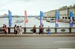 People walk on the bridge across the Neva in St. Petersburg. The bridge is decorated stock photography