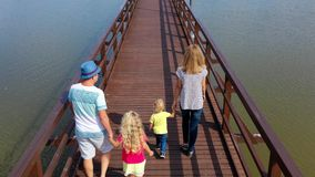 People walk on bridge. Family parents and children. Aerial drone shot stock footage