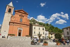 People walk by the central square of the medieval town of Pennabilli, Italy. Royalty Free Stock Images