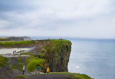 People walk on Cliffs of Moher, west coast of Ireland, County Clare at wild Atlantic ocean, famous tourist attraction. Stock Photography