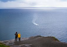 People walk on Cliffs of Moher, west coast of Ireland, County Clare at wild Atlantic ocean, famous tourist attraction. Royalty Free Stock Photography