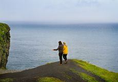 People walk on Cliffs of Moher, west coast of Ireland, County Clare at wild Atlantic ocean, famous tourist attraction. Royalty Free Stock Photo