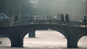 People Walk And Cycle Over Bridge Bokeh stock video footage
