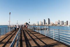 People Walk on the Dock/Pier of Coronado Ferry Landing With Views of San Diego. CORONADO, CALIFORNIA - FEBRUARY 4, 2018: People walk on the dock/pier of the royalty free stock images