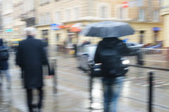 People walk down the street in rain. blurred focus Royalty Free Stock Images