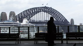 People walk down street in Sydney with cruise ship and Bridge in background stock video