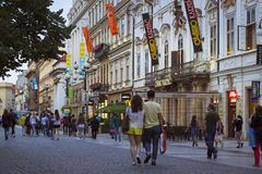 People walk in the evening along the wide street Royalty Free Stock Photos