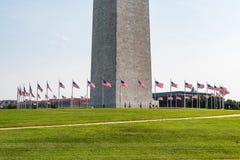 People Walk Among Flags at Washington Monument. WASHINGTON, DC - JULY 12, 2017:  People walk among the 50 American flags encircling the base of the Washington Stock Images