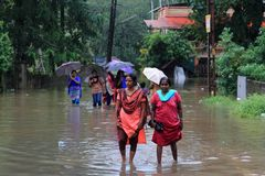 People walk through the flooded roads stock images