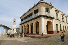 People walk in front of the Brunet palace in Trinidad, Cuba. Stock Photography