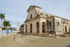 People walk in front of the Church of the Holy Trinity in Trinidad, Cuba. Stock Photos