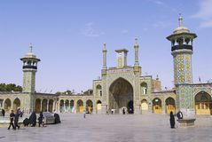 People walk in front of the Fatima Masumeh Shrine in Qom, Iran. Royalty Free Stock Image