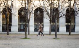 People walk in front of Le Palais Royal in Paris. Lifestyle concept stock image