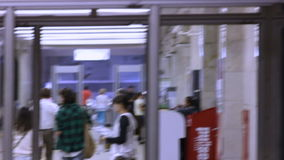 People Walk in Hall with Signs on Wall and Turnstiles stock footage